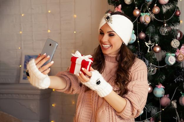 Donna con confezione regalo che comunica tramite chiamata online di smartphone telefono cellulare. celebrazione remota del buon natale