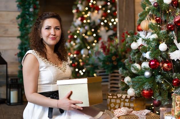Donna con confezione regalo vicino all'albero di natale. interno femminile a casa per il nuovo anno