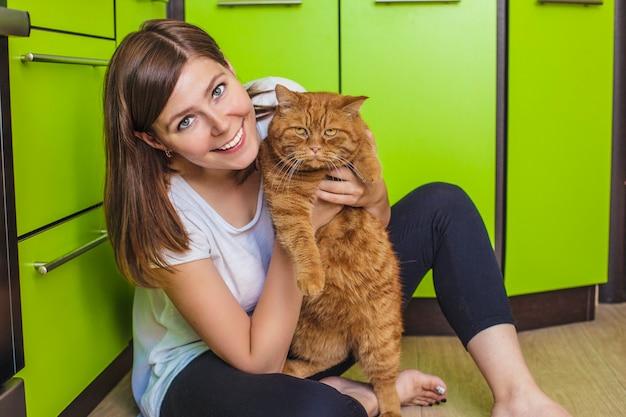 La donna con un gatto rosso tra le braccia che si coccola nella luminosa cucina
