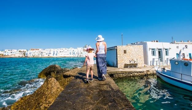 Donna con la ragazza che cammina il pilastro del mare al giorno soleggiato