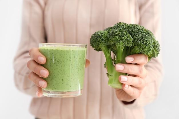 Donna con un bicchiere di sano frullato di broccoli su superficie bianca, primo piano