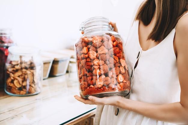 Donna con barattoli di vetro che acquista bacche e frutti secchi in un negozio a rifiuti zero