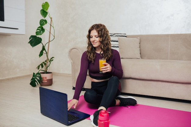 Donna con un bicchiere di succo che guarda il laptop