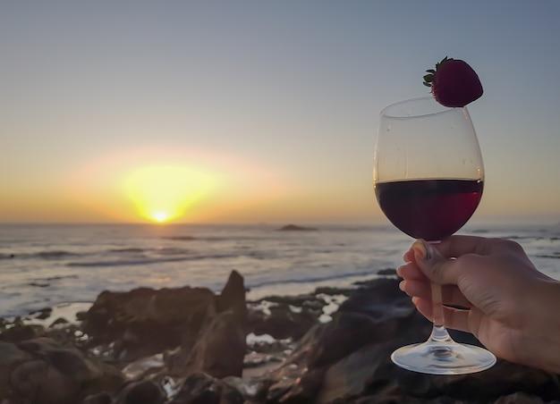 Donna con bicchiere di vino rosso e fragola sulla spiaggia. tramonto meraviglioso