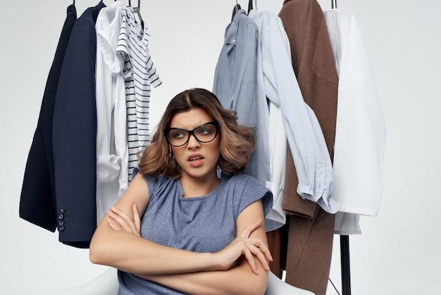 Donna con gli occhiali appendiabiti shopping sfondo chiaro