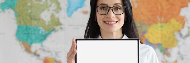 Donna con gli occhiali che tiene in mano una tavoletta digitale vuota sullo sfondo della mappa geografica del mondo