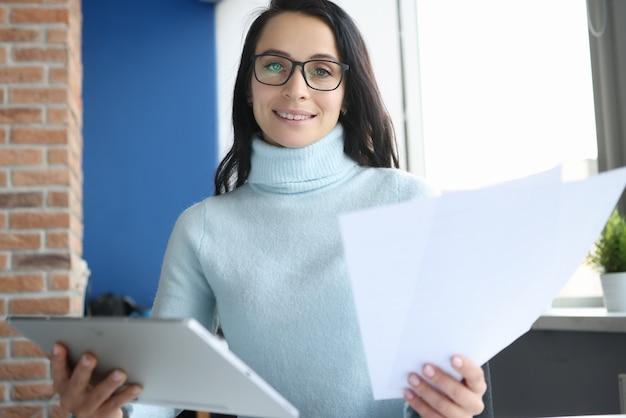 La donna con gli occhiali tiene i documenti in ufficio. concetto di sviluppo di piccole e medie imprese