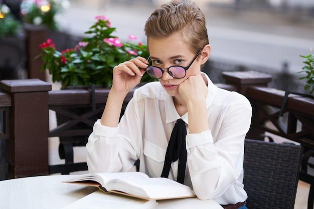 Donna con i fiori del primo piano del ritratto di occhiali nel modello del libro della cravatta della camicia bianca del fondo