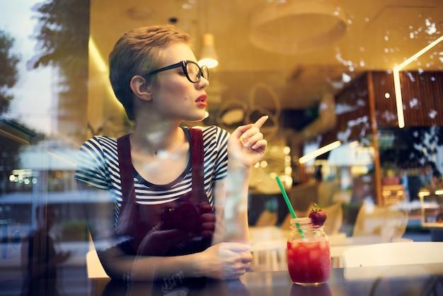 Donna con gli occhiali seduta da sola in un caffè cocktail lifestyle per il tempo libero
