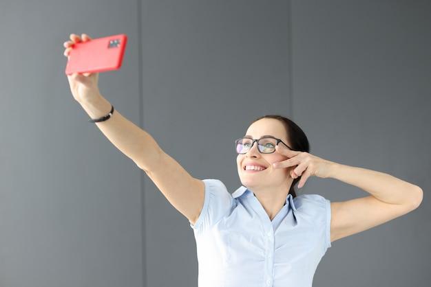 Donna con gli occhiali sorridente e tenendo selfie. concetto di videochiamata