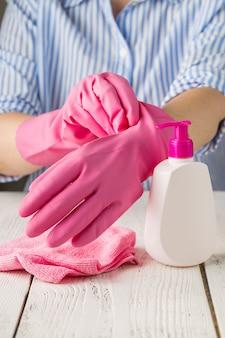 Donna con guanti e prodotti per la pulizia. concetto di pulizia della casa.
