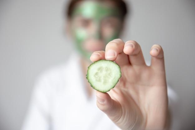 Donna con maschera verde sul viso che tiene in mano una fetta di cetriolo fresco sfondo sfocato