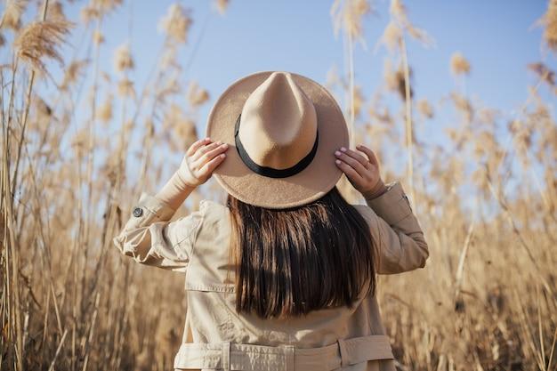 Donna con cappello contro il cielo blu e alte canne secche