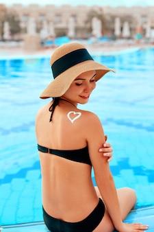 Donna con un cappello sul bordo di una piscina che applica crema solare a forma di cuore sulla spalla abbronzata.