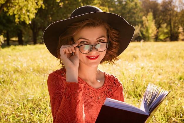 Donna con cappello e occhiali, in un maglione rosso seduto nel parco a leggere un libro