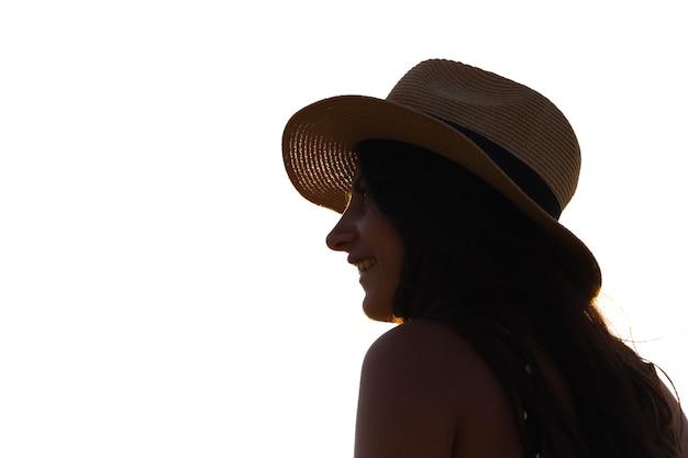 Donna con cappello di profilo guardando l'orizzonte. copia spazio.