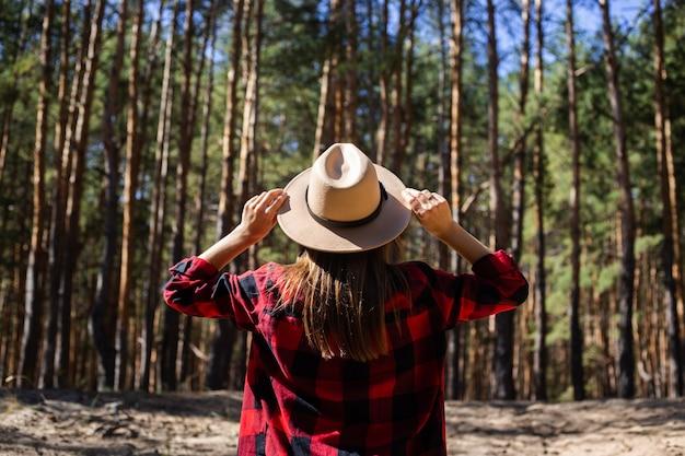 Donna con cappello e camicia a quadri rossa nella foresta.