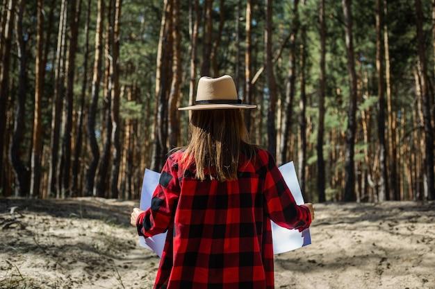 Donna con cappello e camicia a quadri rossa che tiene una mappa nella foresta.