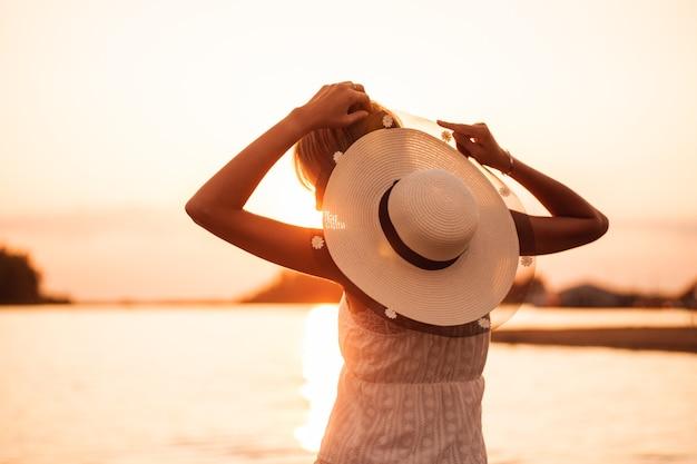 Una donna con cappello al tramonto di profilo una giovane bionda in abito bianco e cappello di paglia decorato con...
