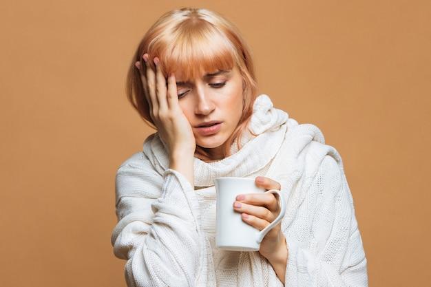Donna con mal di testa, con in mano una tazza di bevanda calda, toccandosi la fronte, avvertendo i primi sintomi dell'influenza Foto Premium