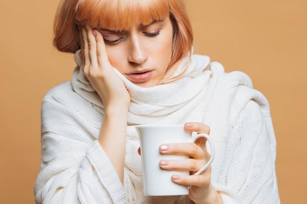 Donna con mal di testa, tenendo una tazza di tè, toccandosi la fronte, avvertendo i primi sintomi dell'influenza