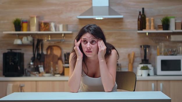 Donna con mal di testa seduta sulla sedia che massaggia le tempie. moglie stressata stanca infelice preoccupata malata che soffre di emicrania, depressione, malattia e ansia sentirsi esausta con sintomi di vertigini