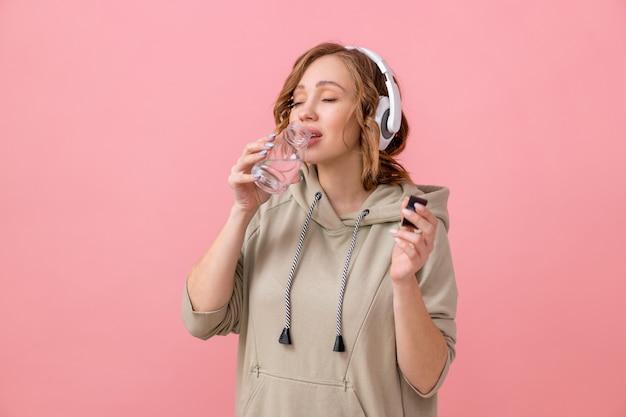 Donna con cuffie vestita oversize felpa con cappuccio bere acqua bottiglia di vetro rosa sfondo studio
