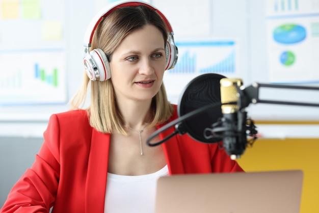 Donna con le cuffie davanti al microfono al tavolo di lavoro