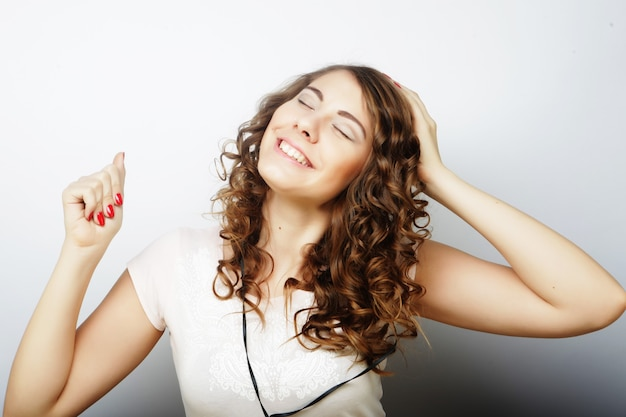 Donna con musica d'ascolto delle cuffie. ragazza di musica che balla su sfondo bianco isolato