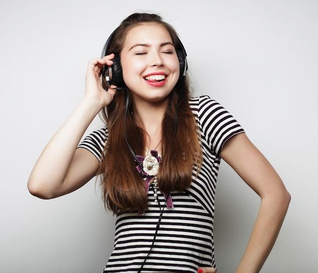 Donna con musica d'ascolto delle cuffie. dancing della ragazza di musica isolato su bianco