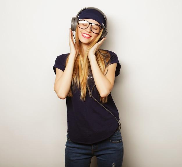 Donna con musica d'ascolto delle cuffie. ragazza dell'adolescente di musica che balla contro il bianco. Foto Premium