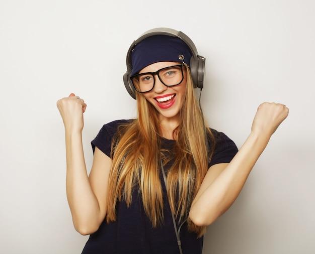 Donna con musica d'ascolto delle cuffie. ragazza dell'adolescente di musica che balla contro il bianco.