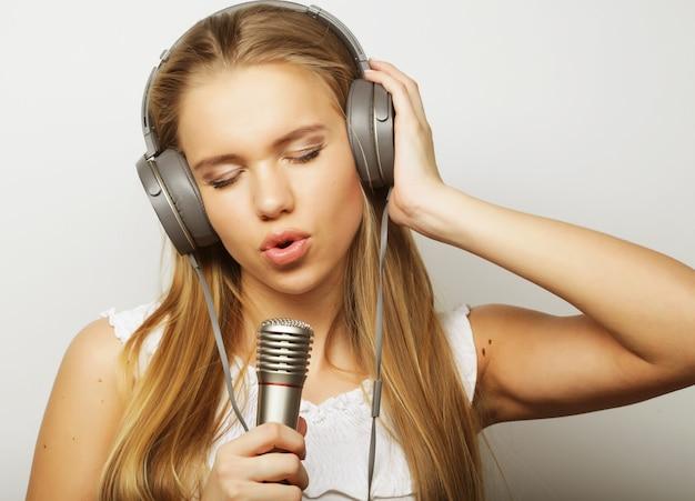 Donna con cuffie e microfoni che ascolta musica e canta