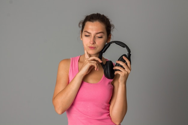 Donna con le cuffie in studio sul muro grigio