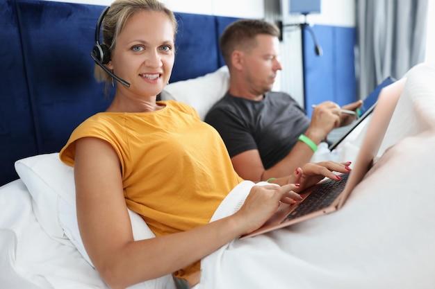 Donna con le cuffie con microfono sdraiata a letto con il computer portatile accanto al lavoro a distanza del marito