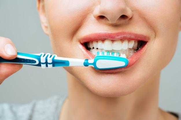 La donna con i denti bianchi sani tiene uno spazzolino da denti e sorride il concetto di igiene orale