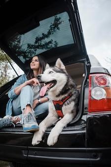 Donna con il suo adorabile cane husky che viaggiano in auto