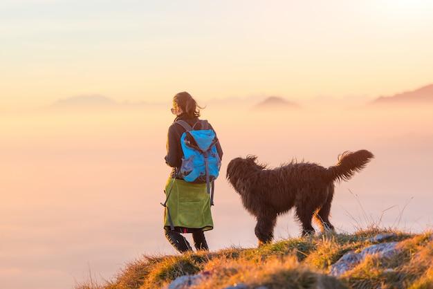 Donna con il suo pastore nero che cammina in montagna