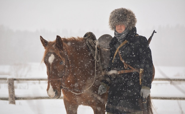 Donna con il suo cavallo marrone in inverno