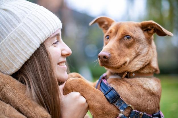Donna con il suo cane in autunno in un parco. le zampe del cane nelle mani della donna, lei lo guarda e sorride.