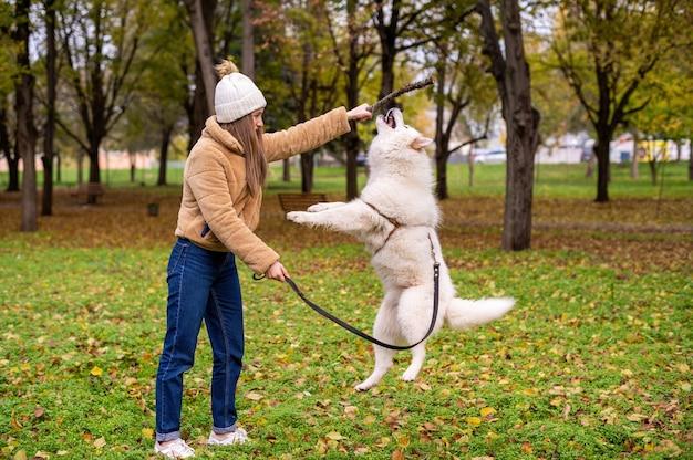 Donna con il suo cane in autunno in un parco. la donna sta giocando con il cane usando un bastone, il cane sta saltando. vegetazione intorno