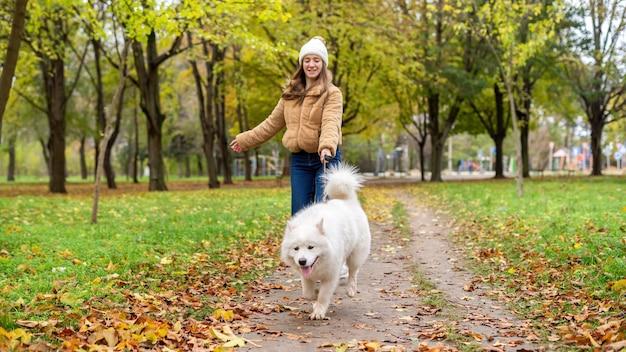 Donna con il suo cane in autunno in un parco. la donna sta camminando e tenendo il guinzaglio. foglie ingiallite a terra Foto Premium
