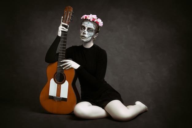 Donna con il viso dipinto come una catrina e fiori tra i capelli su sfondo scuro con in mano una chitarra. giorno della morte
