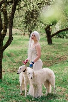 Donna con i suoi cani di wolfhound russi in giardino
