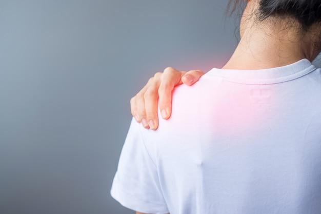 Donna con distorsione alla spalla, dolore muscolare durante il superlavoro. ragazza che ha problemi con il corpo dopo il risveglio. dolore alla spalla, dolore scapolare, sindrome dell'ufficio e concetto ergonomico