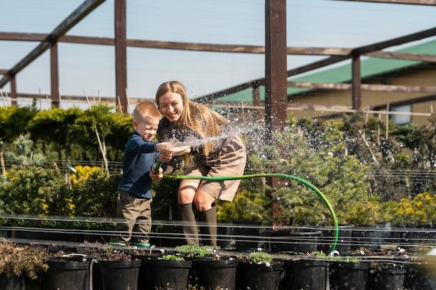 Donna con suo figlio che innaffia i vasi delle piante con un tubo flessibile