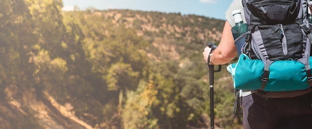 Donna con attrezzatura da trekking a piedi nel verde paesaggio di montagna in una giornata di sole