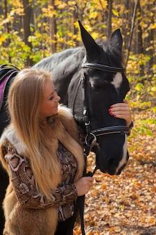 Donna con un cavallo per una passeggiata nella foresta d'autunno