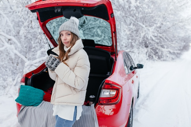 Una donna con caffè caldo in mano si siede in una macchina rossa in una giornata invernale di neve nella foresta. una ragazza con una tazza di caffè caldo è seduta in una macchina con il bagagliaio aperto