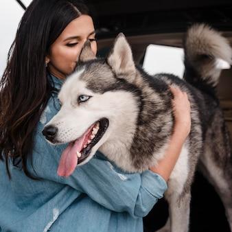 Donna con husky che viaggiano in auto